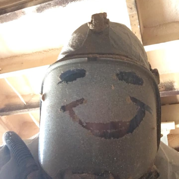 A dusty protective face mask with a happy face drawn in the dust.